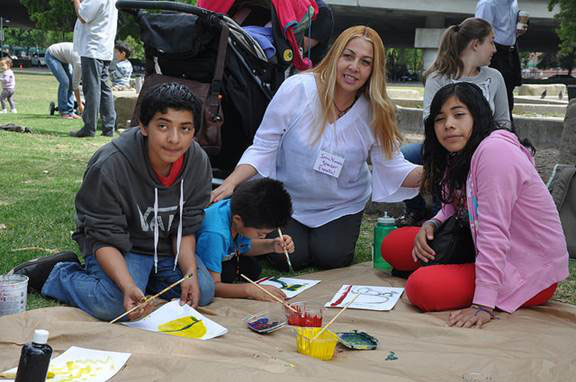 Irma Navarro, parent leader with Services Immigrant Rights Education Network, with kids painting their vision of California with $9 billion more each year from property tax reform. (Photo by CultureStike/Jess Cook)