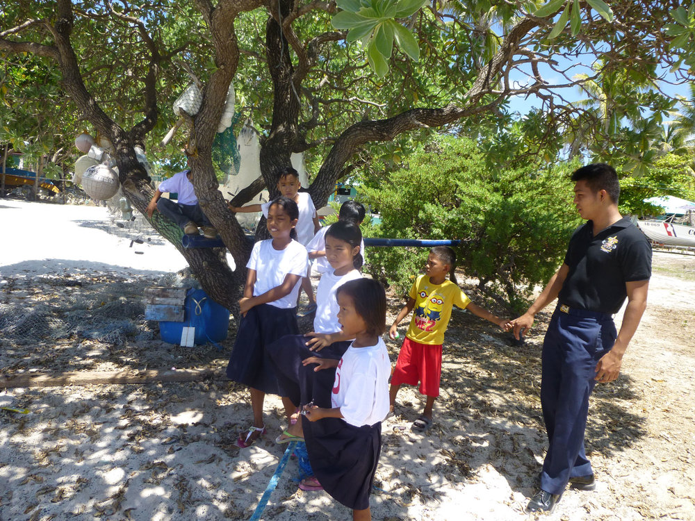 A Coast Guard teacher takes the children for a stroll by the beach (Photo by Criselda Yabes)
