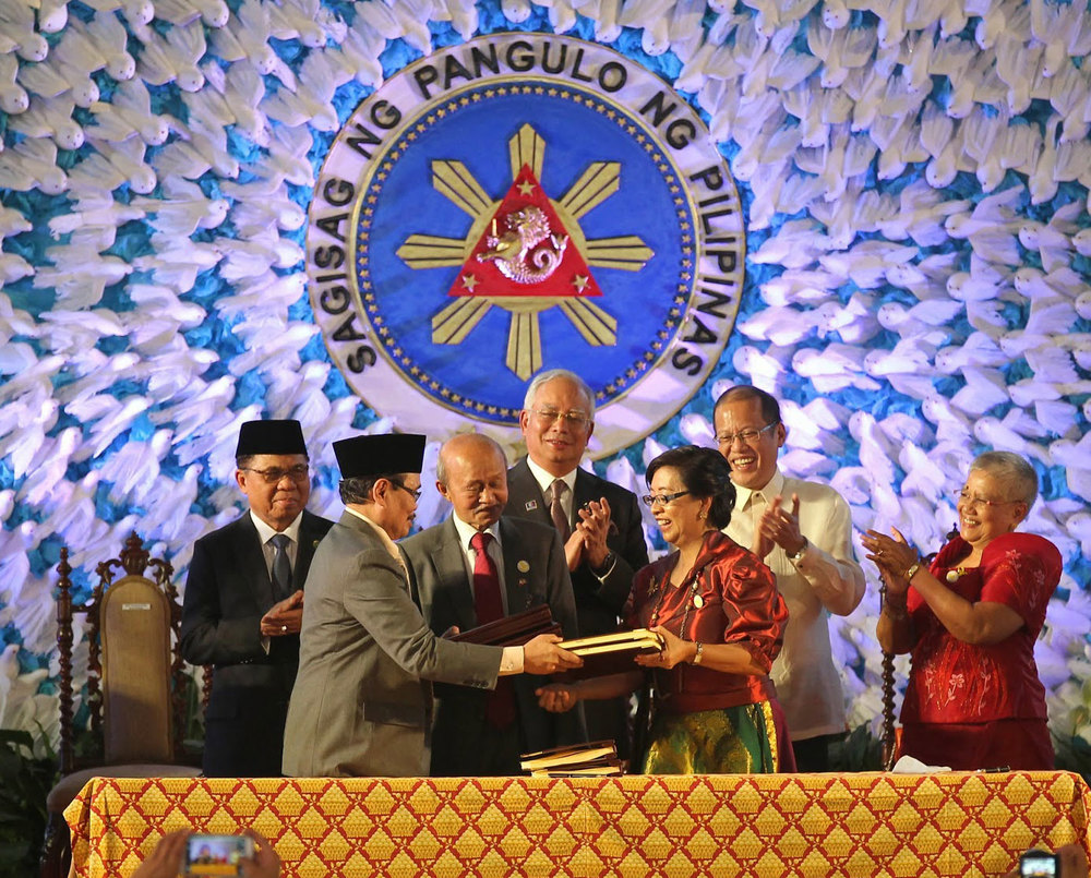 President Benigno Aquino III (back, second from right) and Malaysian Prime Minister Najib Razak (back, center) applaud as peace panel heads Mohagher Iqbal  and Miriam Coronel-Ferrer shake hands after the signing of the Comprehensive Agreement on the Bangsamoro at Malacañang last March 27, 2015 (Photo by Gil Nartea, Robert Viñas, Rodolfo Manabat, Malacañang Photo Bureau)