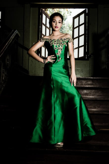 Emerald-green off-the-shoulder gown made of mikado silk with a serpentine silhouette and accentuated with beaded laser-cut baroque pattern on the bodice and sleeves. Faux sapphire blue stones are scattered for color accent. (Model: Patricia Matabilas. Photo by Beauford Ma)