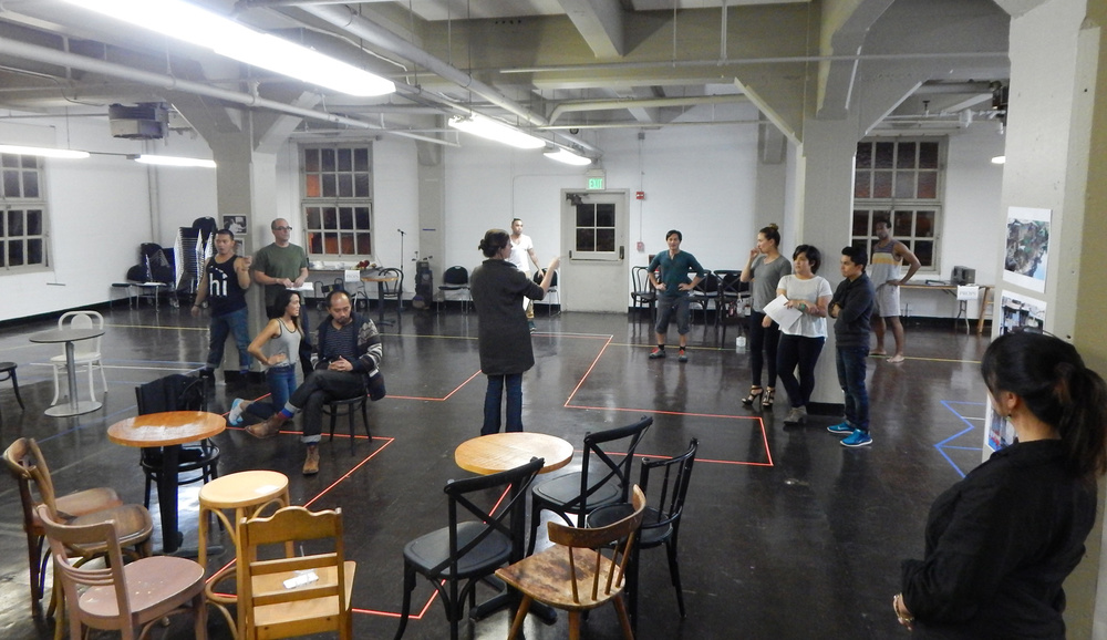 """Dogeaters"" rehearsal. From left to right: Melvign Badiola, Lawrence Radecker, Christine Jamlig (kneeling), Jomar Tagatac (seated), Loretta Greco (director), Mike Sagun, Ogie Zulueta, Charisse Loriaux, Julie Kuwabara, Jed Parsario, Raphael Jordan, Esperanza Catubig. (Photo by Lily Sorenson)"
