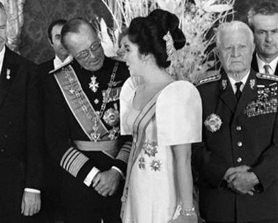 Imelda conversing with Prince Bernard of the Netherlands and the tiara which ended up on the back of her head. Title or no title, Imelda was going to wear a tiara to the ball—even if in the most unlikely place.
