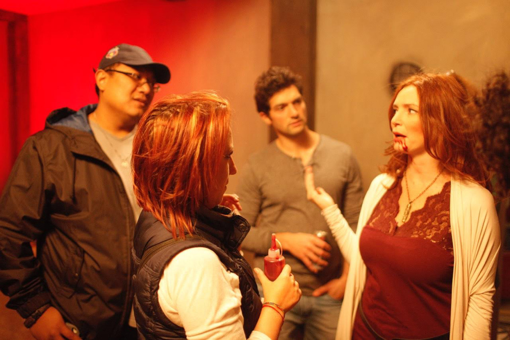 "Mark Lagrimas (left) giving feedback during the production of ""They're Watching."" With makeup artist Andreea Tesdall (second from left) and stars David Alpay and Brigid Brannagh (Photo by Sorin Nainer)"