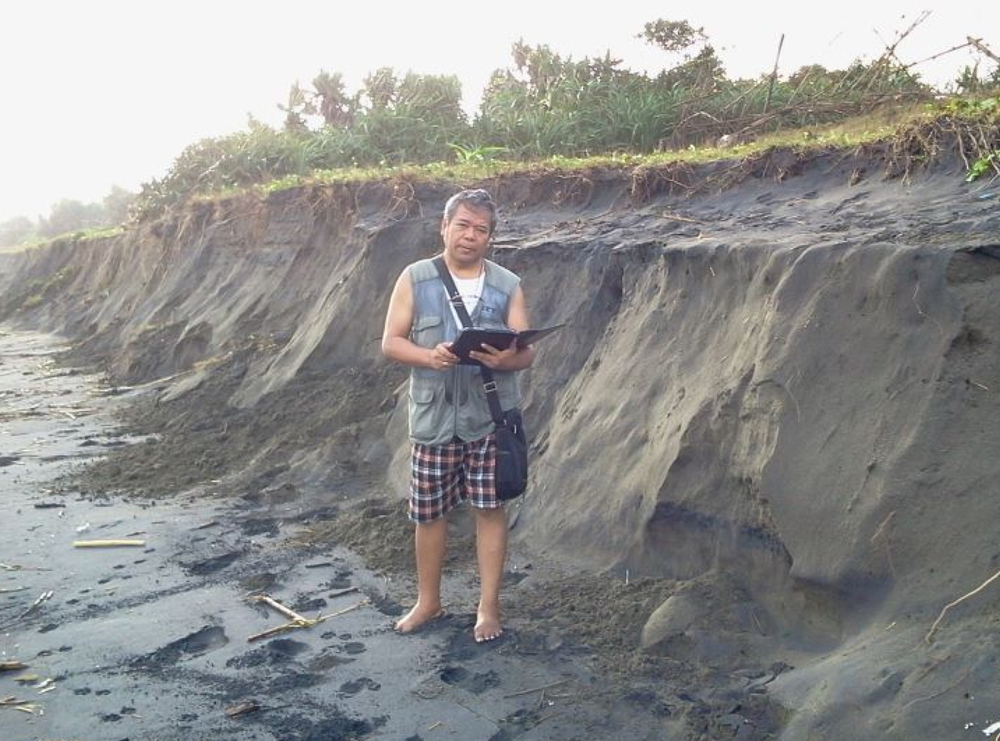Jun Collado, Ph. D., poses beside the abrupt drop in the elevation of the Ballesteros beach. It is caused by black-sand mining. (Photo courtesy of Jun Collado, Ph. D.)