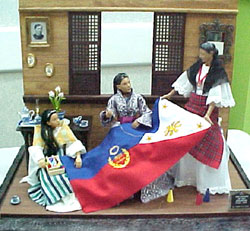 Still another image (a doll diorama) showing the Philippine Flag with the wreath escutcheon in the center more clearly.