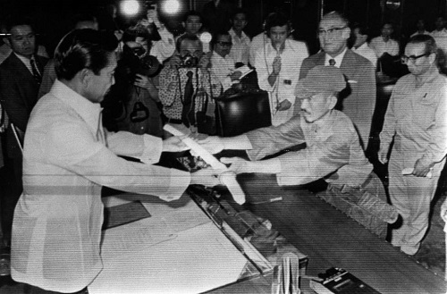 The picture shows Japanese lieutenant Hiroo Onoda formally surrendering his sword to President Marcos on March 11, 1974 at Malacañang Palace.