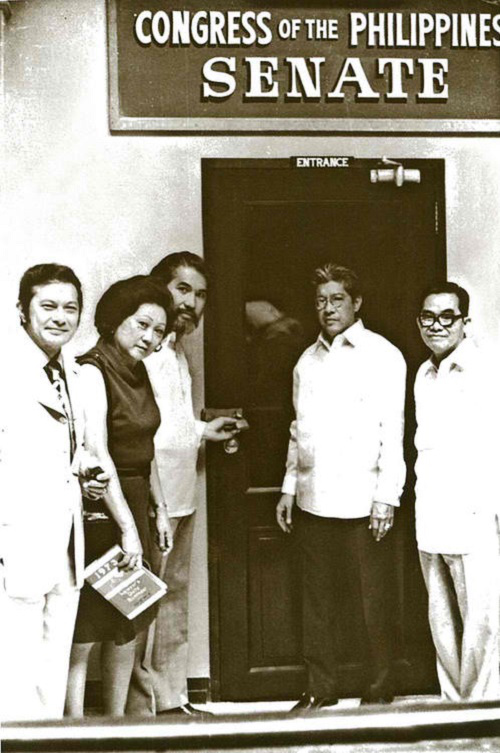 The photo depicts Senators Doy Laurel, Eva Estrada Kalaw, Ramon Mitra, and Jovito Salonga posing in front of the Senate session hall which had been padlocked, a stark symbol of power held by a single man.