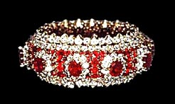 "One of the smaller baubles, from the Roumeliotes collection. Ruby and diamond bracelet with ten 5 cts. pigeon blood red rubies surrounded by smaller rubies and diamonds in yellow gold. 1.5 inches wide X 8"" long.  Marked Van Cleef & Arpels, NY. Item# 36, page 5 PI customs list. (Photo courtesy of Diana Limjoco)"