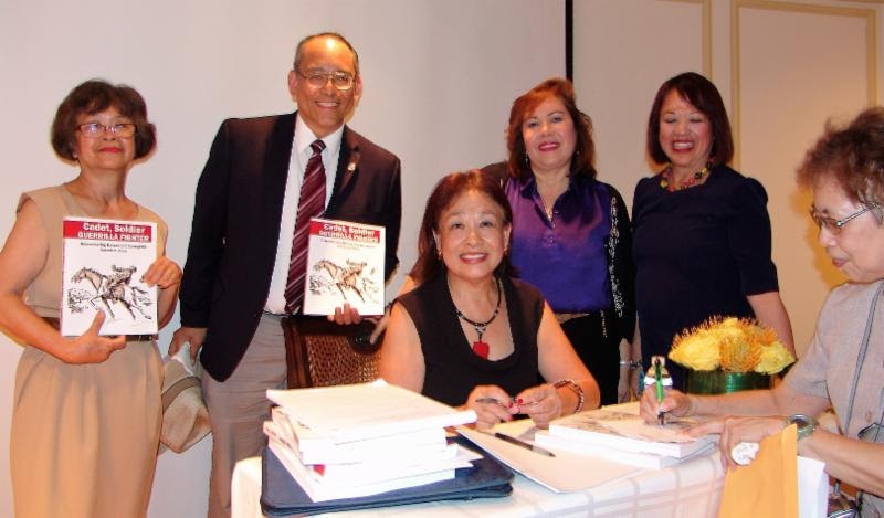 Book signing: Editor Pepi Nieva (seated center) with Mitzi Pickard (moderator and panel organizer), Ronie Nieva, and members of the Filipino American community.