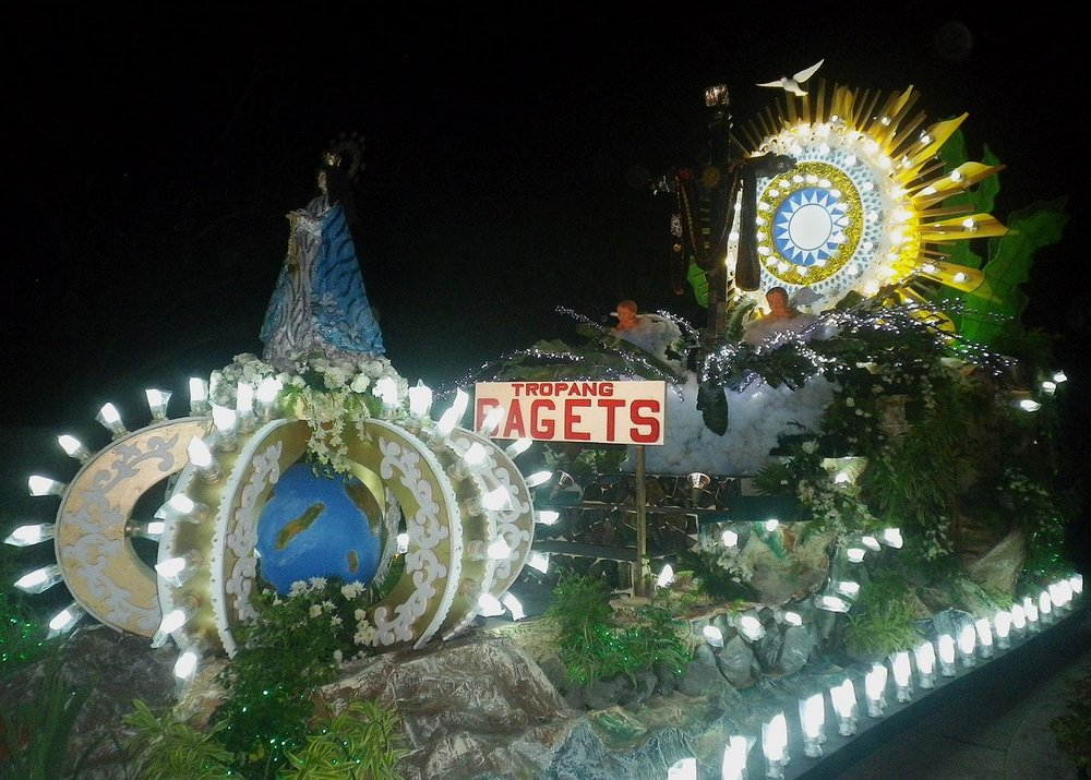 Ancient faith meets popular culture: the iconic symbol of Cupang's religious devotion is the 'Mahal na Poon', whose cross does not bear a crucified figure but a symbolic sun with a human visage. A youth civic group called Tropang Bagets borrowed this elaborate carriage from the nearby town of Alitagtag, 'carroza capital of the Philippines'. (Photo by Ed Maranan)