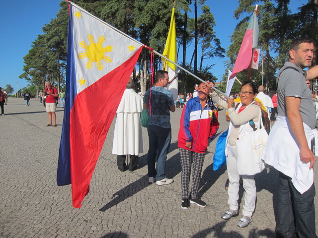 Getting ready.  Myrna Galiza, right, gets ready to carry the Philippine flag in the procession. She has been living in Lisbon for 28 years and has been joining the procession for many years. With her is her friend, Belen.