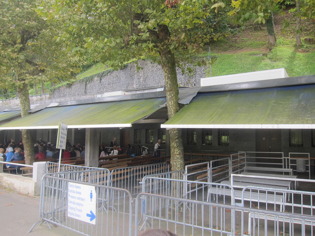 The entrance to the baths.  There are 17 baths in total, 11 for women and 6 for men, with each section containing a small bath for children. The water at the baths is a constant 12 degrees centigrade. Lourdes water draws many devotees, many of whom have claimed to have been cured by drinking or bathing in it. The baths and water are free of charge to anyone.