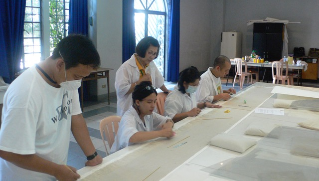 Members of ACES, a team Dalisay established in 2001, work on a Botong Francisco mural.