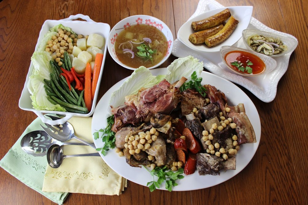 Spanish Cocido - the full spread of various meats with the sides of clear soup broth, vegetables, eggplant and tomato sauces, and the sweet plantains. (Photography by Elizabeth Ann Quirino)