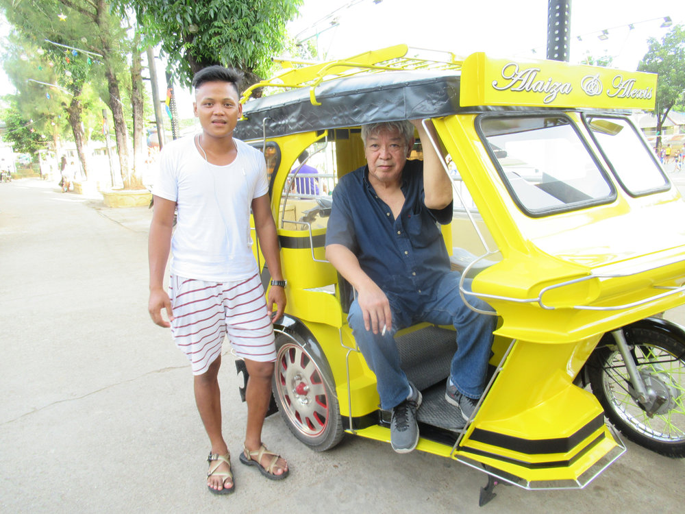 Bert and our tricycle driver-cum-tour guide proudly posing with his brand new ride. (Photo by Bella Bonner)