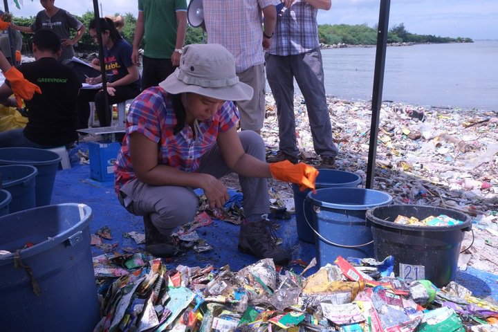 Lea Guerrero, climate and clean energy campaigner of Gaia (Global Alliance for Incinerator Alternatives) Asia Pacific takes a closer look at the branded plastic packaging waste found on Freedom Island. (Photo by Miko Aliño, GAIA ASIA PACIFIC)
