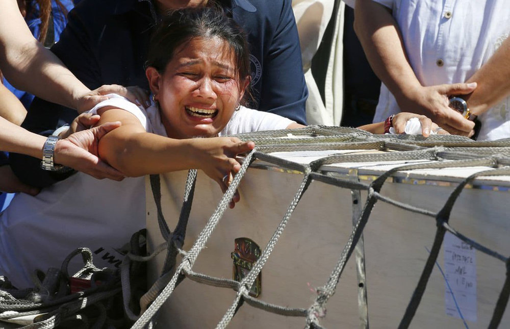 Jessica Demafelis cries over the remains of her sister Joanna which arrived in Manila (Bullit Marquez/AP)