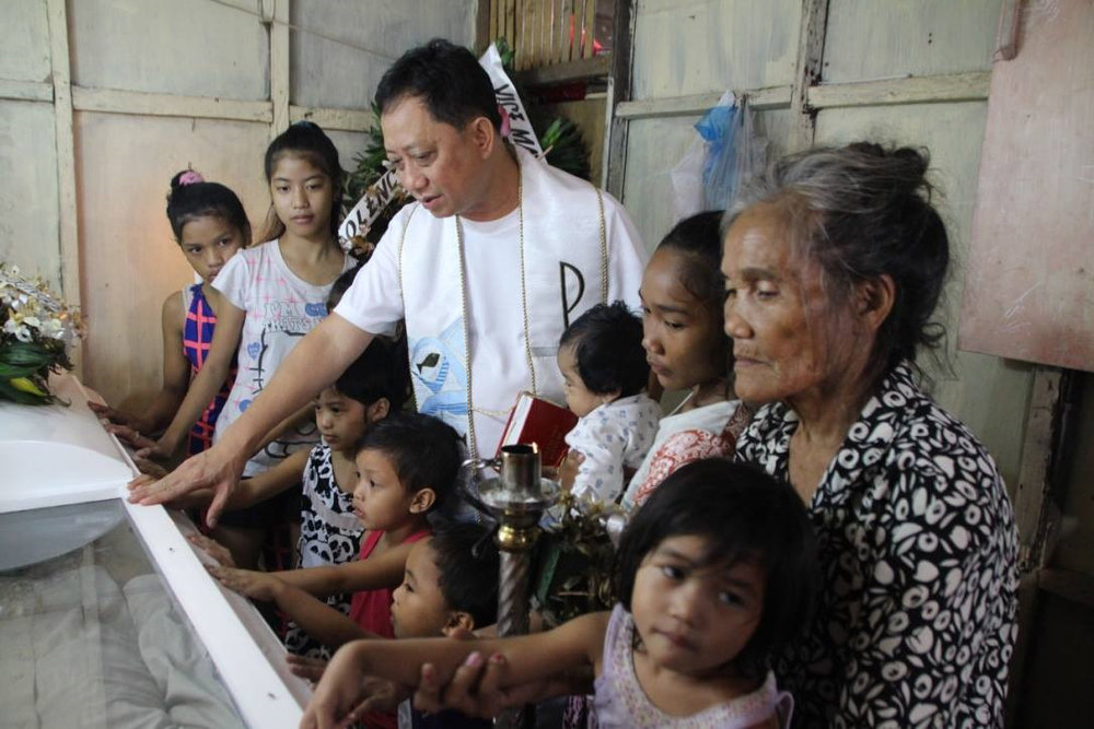 Father Danny with Lola Remy and her grandchildren at Juan's wake (Photo courtesy of Father Danny Pilario)
