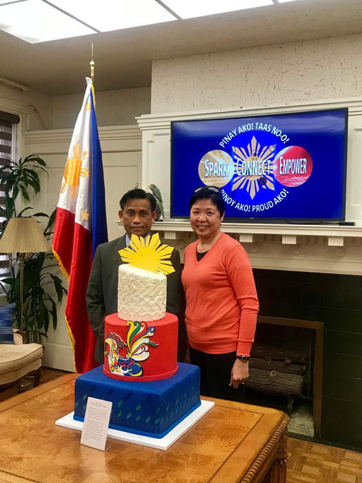 "Consul General Henry Bensurto, Jr. stands behind the ""Pinoy Pride"" cake created by Bettina Santos Yap."