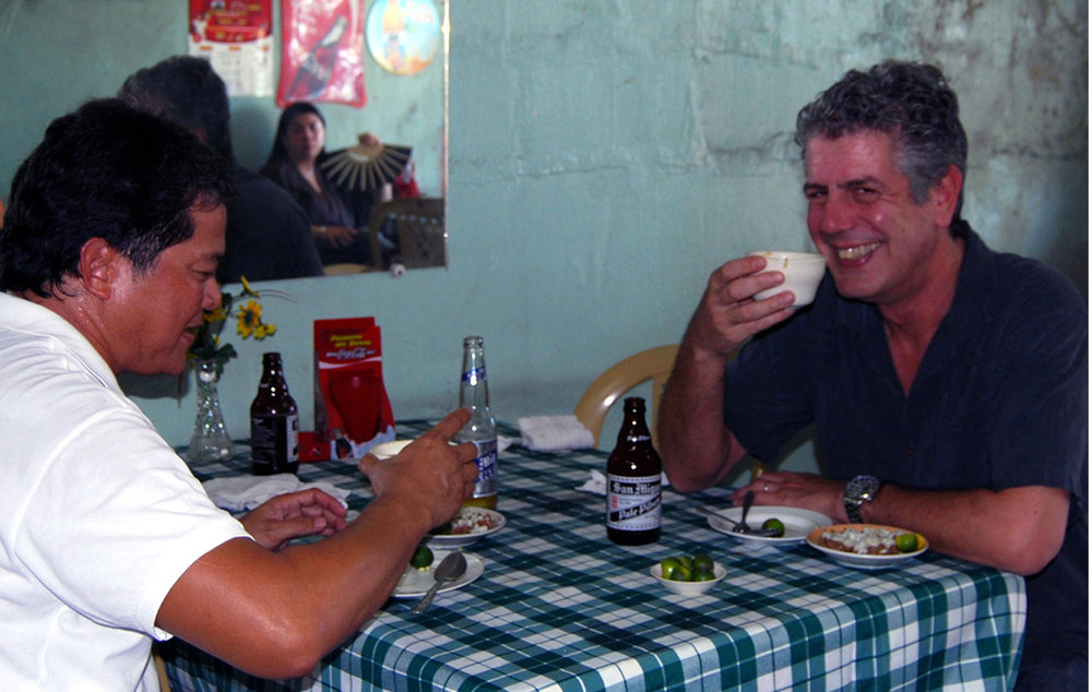 Anthony Bourdain relishing the last drop of  papaitan  (bitter soup with goat's innards and bile) with the author in a goat shack in Angeles City, October 2008. (Photo courtesy of Claude Tayag)