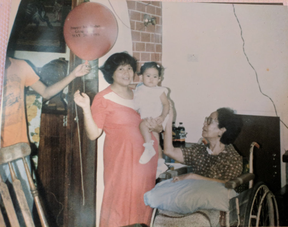 Mayo being carried by her pregnant mother next to her grandmother (in wheelchair) whose house she was born in (Caloocan City, Metro Manila, May 1986).