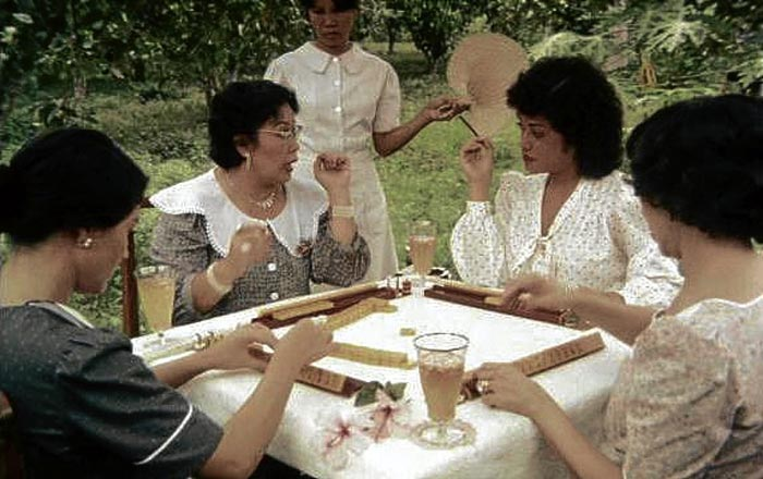 """Upper class Filipinas"" engaged in a game of mahjong. This is a scene from the 1982 Filipino film,  Oro, Plata, Mata . The actresses are (left to right) Liza Lorena (partial view), Lorli Villanueva, Mitch Valdes and Fides Cuyugan-Asencio (partial profile)."