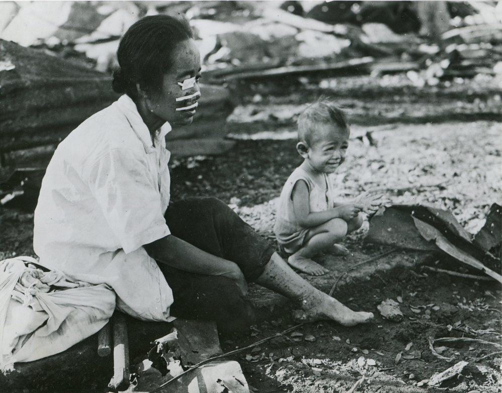 A Filipino woman, wounded in the face and eye by shrapnel, waits with her child in front of the family's burned home in Paco for help across the Pasig River. (National Archives)