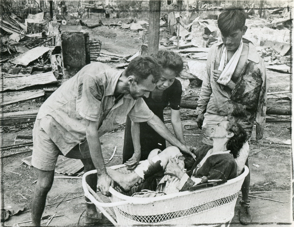 A resident of Manila, wounded during the fighting for the Philippine capital, is placed in a basket by neighbors for transportation to a first aid station. (National Archives)