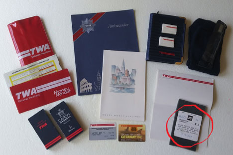 Mementos and souvenirs of my high-flying days with TWA, including a Money Converter slide-rule, First Class-Business Class menus, amenities kit, credit cards, stationery, etc., 1980-'90s. Encircled item in lower right corner is the Hertz stub from when I did the quick In-Out rental @ Heathrow. (Photo by the author)