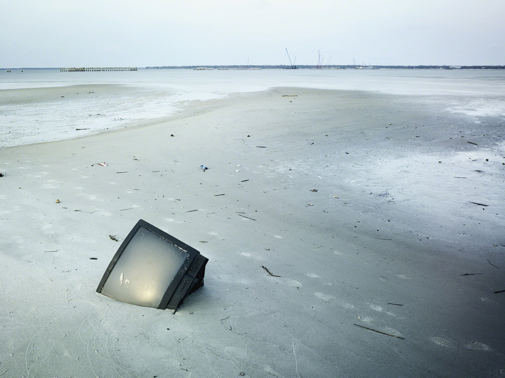TV in the sand post Hurricane Katrina, Bay St. Louis, Mississippi. © Stephen Wilkes courtesy of Peter Fetterman Gallery.