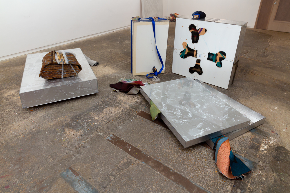Understudies (2015). Acrylic, aluminium tape, chipboard, Jacquard tapestries, lavatory stall screen, MDF, paint, paper, paper tape, photographers' tape, ratchet strap, wooden bed parts. Courtesy Nigel Massey. Photograph: Peter White