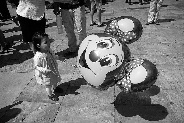 Small child outside Small World ride, Walt Disney. By Piotr Mamnaimie [CC BY 2.0], via Flickr