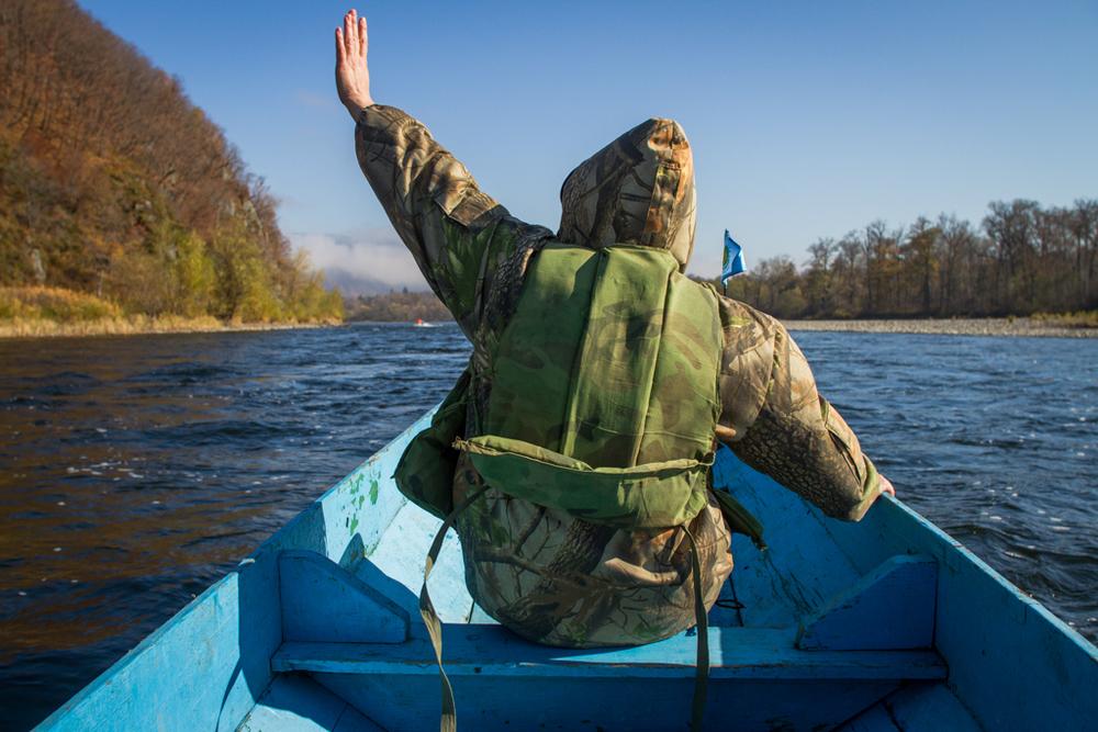 Olga Vasilievna, Communication Specialist for Udege Legend National Park, waving to fisherman on shore.