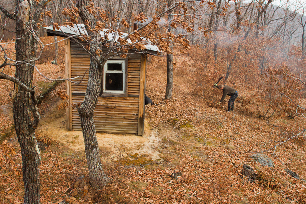 There are over 60 Inspectors' cabins and outposts throughout the Reserve. A 28 year-old Inspector, Evgeni, cuts brush from around a cabin that overlooks several points of the highway, which bisects the Reserve. From here, the Inspectors can listen for gunshots and see if there are any suspicious vehicles on the road.