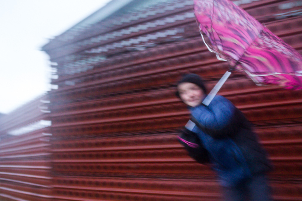 A young Russian boy fights the wind and the rain, on his morning walk to school.