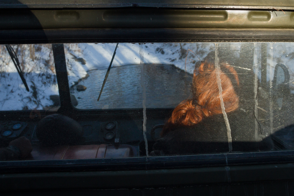 Driving into the boreal forest at dawn. Tasia Palkina sits up front in the cab of a retired Russian military truck. The roads traversing the interior of the park are only accessible by off-road vehicles with many deep river crossings.