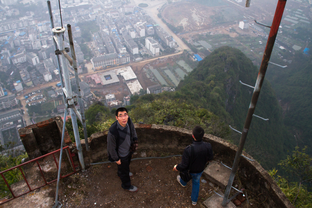 Zhuoyue English College students: David (left) and Andy look over Yangshuo, from the T.V tower west of town.  The College requires the students to take English names and to speak only English while attending school. Andy was sent to the college by his employer, a French international company that specializes in manufacturing wall outlet covers. David is studying English with the hope of opening his own business.