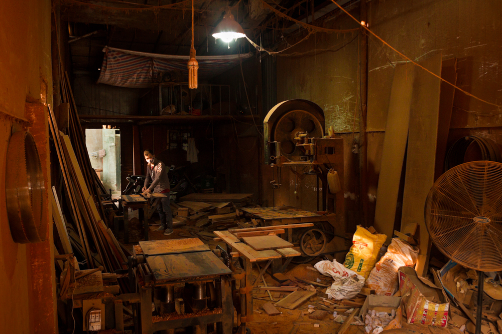Workshops and showrooms fill every building, lining both sides of the streets of the village boroughs outside Hanoi. In the workshops, the red sawdust of the rosewood lays everywhere and fills the air.