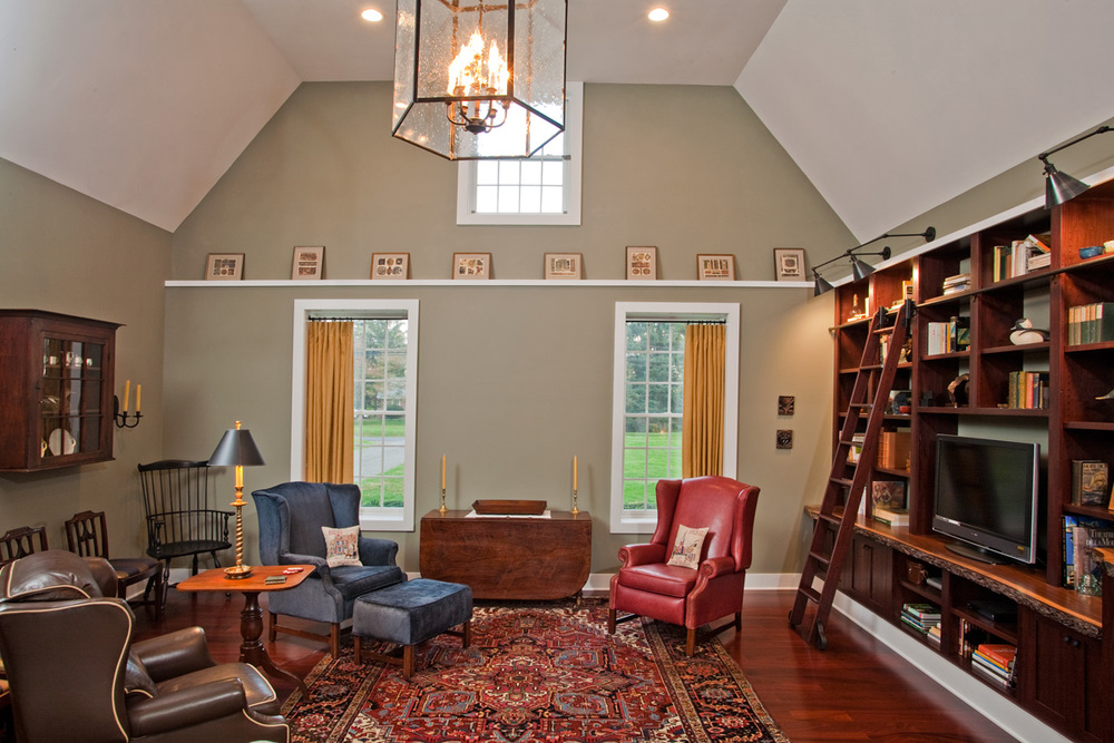 High ceilings in contemporary cape are brought to a more intimate scale by the architects use of a ledge trimmed in white molding surrounding most of the room, including the top edge of custom crafted built ins which feature natural bark end grain countertops and a library ladder.  Color palette is drawn from Heriz rug,  slipcovered wing chair and ottoman, box pleat linen drapes, oil rubbed bronze hardware and lighting, birdcage chandelier and library lights