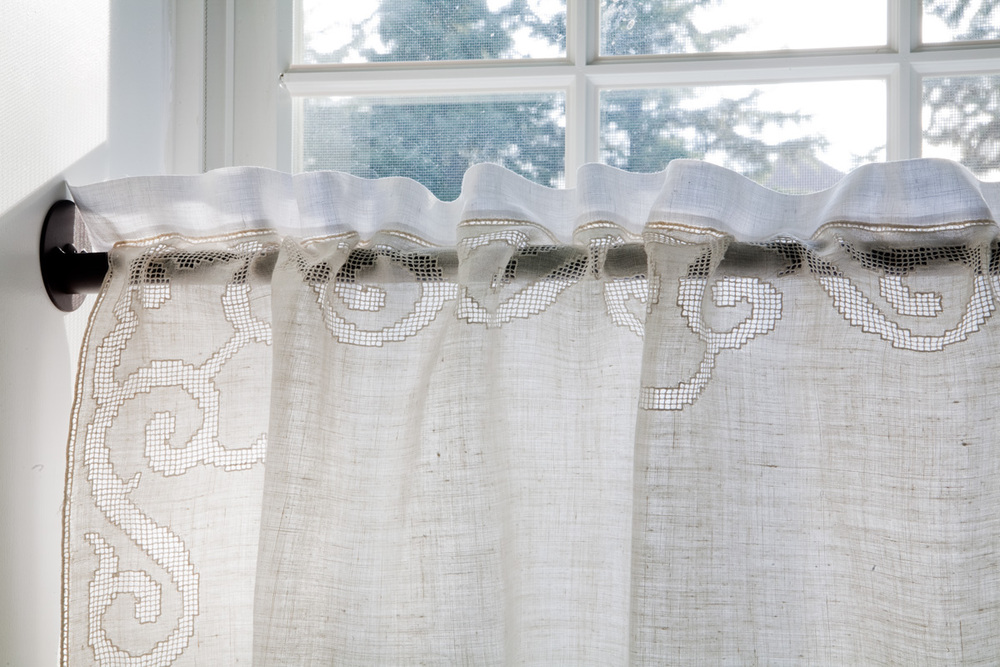 Two vintage table cloths are layered to create a casing for hanging on skinny iron rod and for subtle mix of bright white and cream to tie in with room scheme