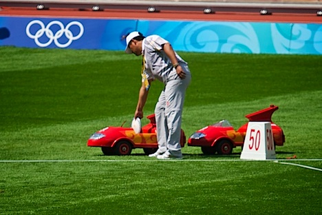 The thrown discus is placed in the red RC car for return to the front