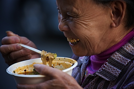 Old woman eating noodles