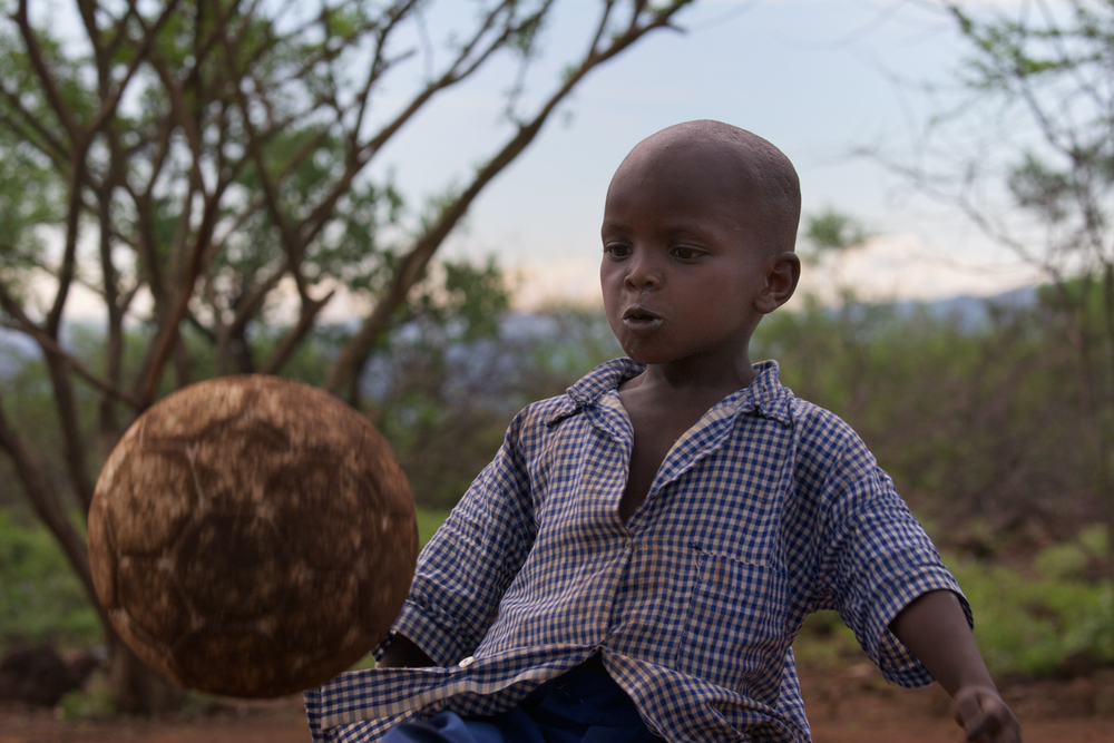 A young Pokot child plays with a very well loved football (soccer ball)