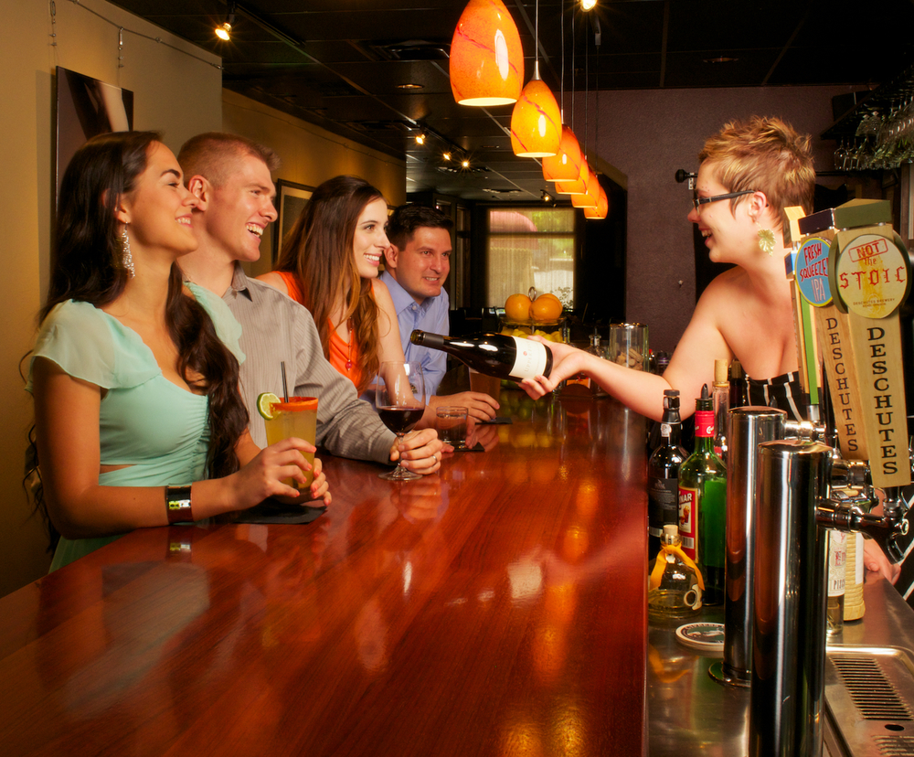 A staged photo with models to highlight happy hour, the variety of drinks available, the look of the bar, and so-on