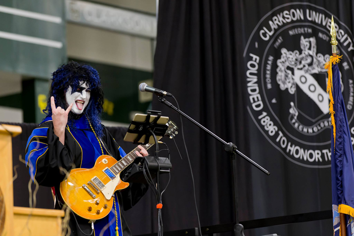 Clarkson University Associate Professor of Civil & Environmental Engineering supports speaker John Elder Robison, creator of KISS guitar sound effects, at Clarkson's 2015 convocation.
