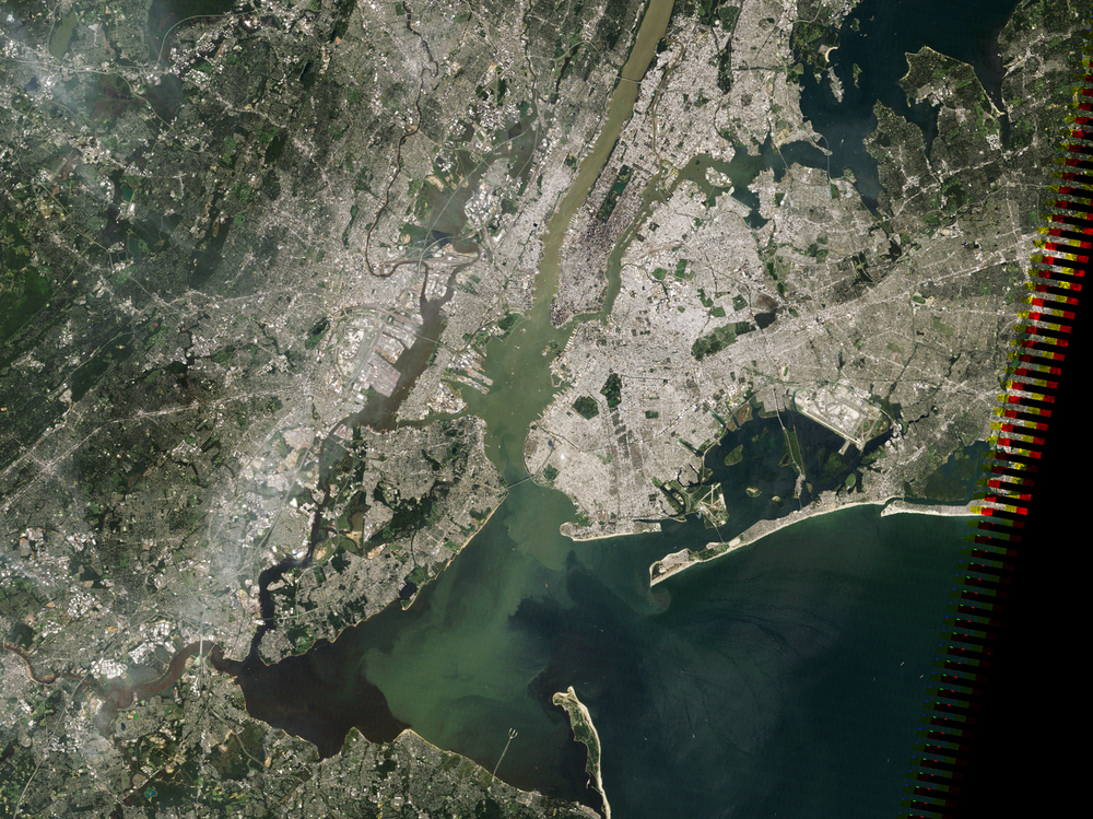 In this true-color, NASA satellite image, sediment plumes - the pale green and tan water flowing past Manhattan - mix with the darker waters of New York Harbor and the Atlantic Ocean