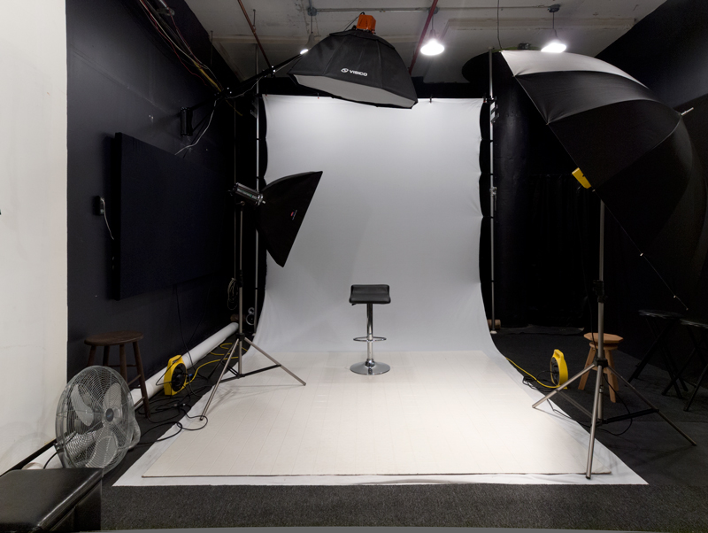 Basic shooting area features white wrinkle-free Westcott white backdrop and paper hangers. Wall mounted overhead boom light.