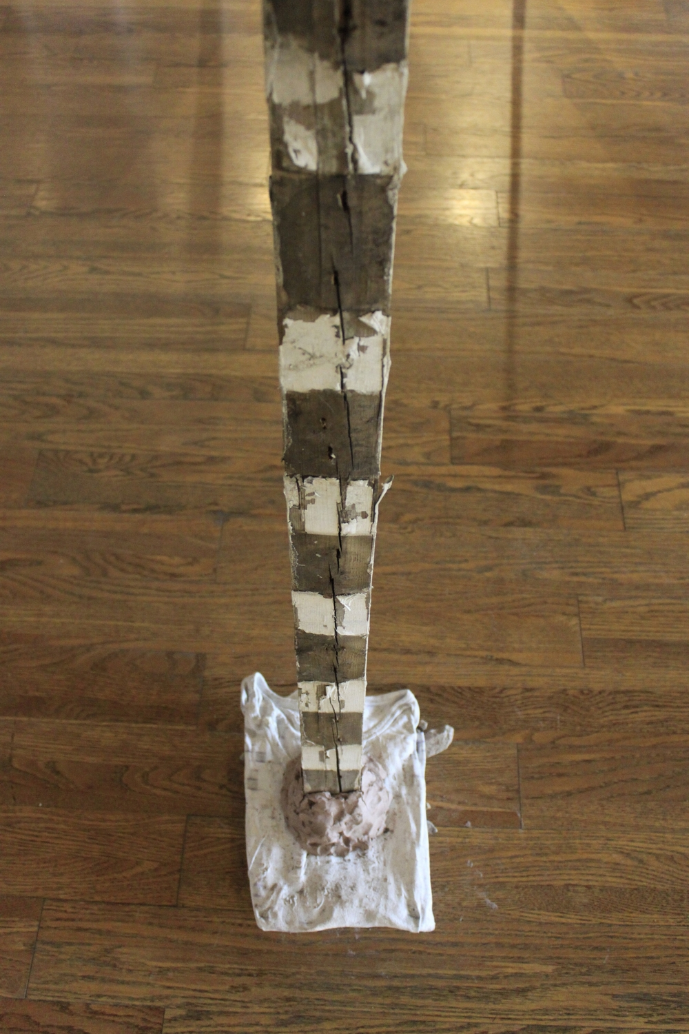 """A dumb blankness, full of meaning  180"""" x 2.5"""" x 1""""  2015  Wood, wire, epoxy, clay, rock, shirt, paint"""