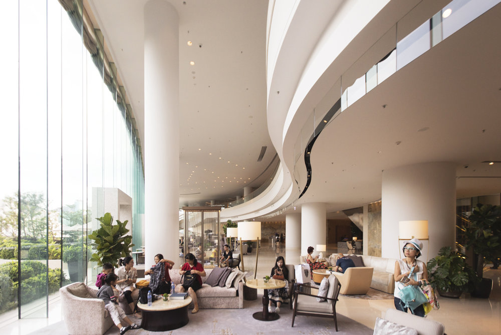 The lobby's curved glass windows span 26 feet-foot-tall windows will link the manicured outdoors with the interior design
