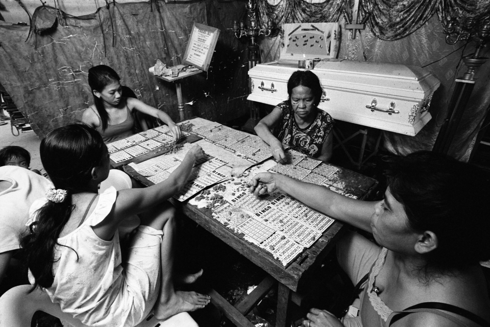 Women play bingo to raise money for a funeral in Manila, Philippines.